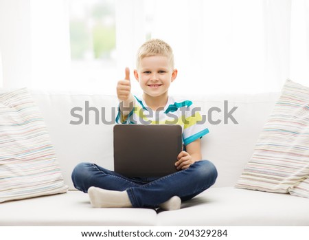 home, leisure and new technology concept - smiling little boy with tablet pc computer at home showing thumbs up - stock photo