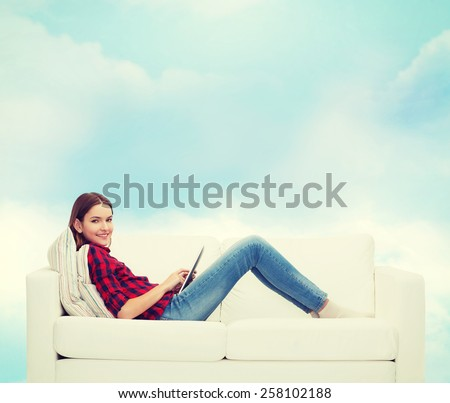 home, leisure, technology and happiness concept - smiling teenage girl sitting on sofa with tablet pc comuter