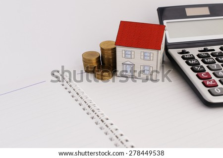 Home loans concept with paper house and coins stack and calculate on book pages - stock photo