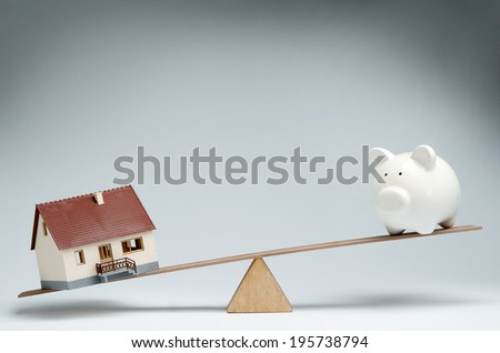 Home loans market. Model house and piggy bank balancing on a seesaw - stock photo