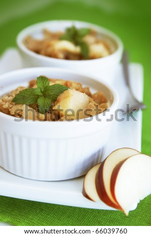 Home made apple crumble in a white container on a green background - stock photo