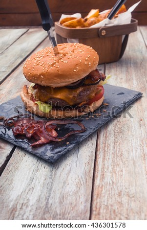 Home made bacon cheese burger with angus beef, tomatoes, onions, cheddar cheese, potato cuts in basket. On slate plate and vintage styled wooden table. - stock photo