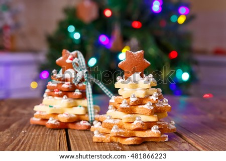 Home made baked Christmas gingerbread tree as a gift for family and friends on wooden background. With colorful lights from Christmas tree on background. With icing sugar as snow.