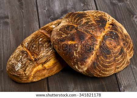 Home-made bread loaves of different flavours on wooden table background - stock photo