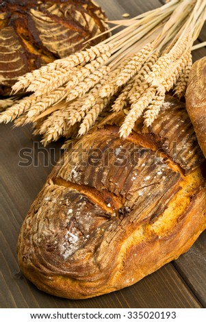 Home-made bread loaves of different flavours with wheat ears on wooden table background