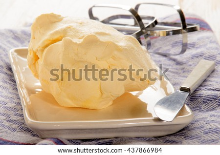 home made butter and a butter knife on plate - stock photo