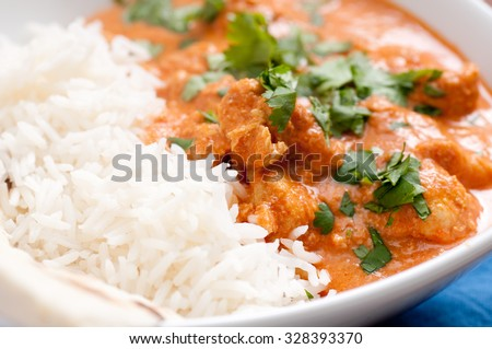 home made butter chicken and fresh naan bread on the side stock photo - stock photo