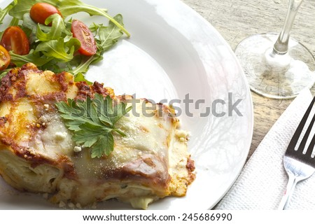 Home made cheese lasagna with arugula salad and a glass of red wine - stock photo
