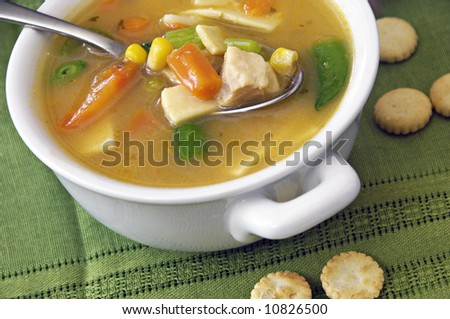 Home-made chicken and vegetable soup with oyster crackers. - stock photo