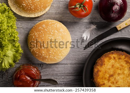 Home made chicken burger with lettuce, tomato and onion on wooden board - stock photo