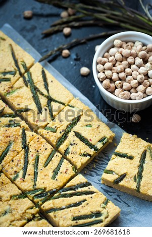 Home made chickpea pie also know as socca with wild asparagus - stock photo