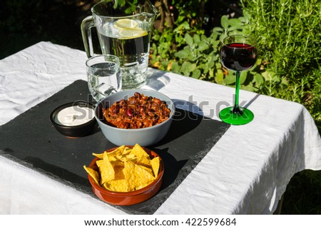 Home made Chilli Con Carne in orange ceramic bowl and tortilla chips and soured cream on the side with jug and glass of iced water. On slate mat, outside on linen covered table. - stock photo