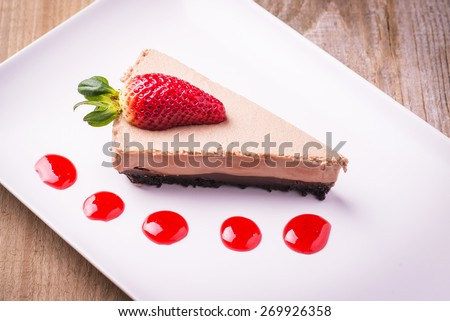 Home made chocolate cake slice and strawberry topping and fruit - stock photo