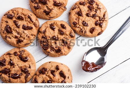 Home made chocolate cookies and spoon on white wood background - stock photo