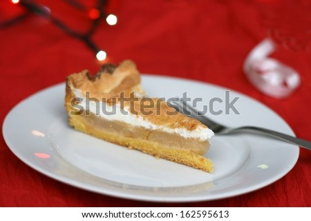 Home made christmas apple pie with whipped egg white, christmas lights and decoration in the background, shallow DOF