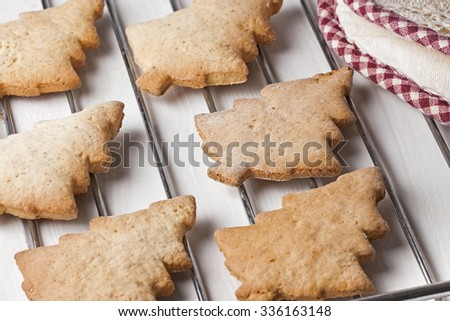 Home made christmas tree biscuits on oven reck and pot holder on white wooden table - stock photo