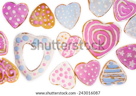 home made cookies in shape of hearts covered with pink and white icing for Saint Valentine's day