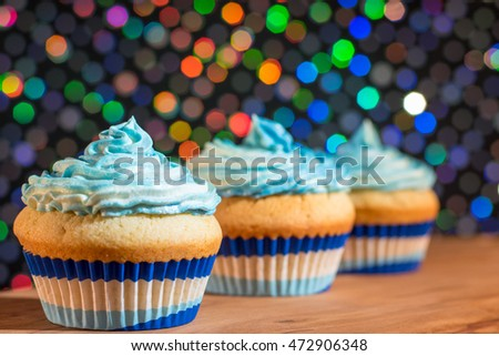 Home made cupcakes with blue and white swirl frosting with coloured bokeh background