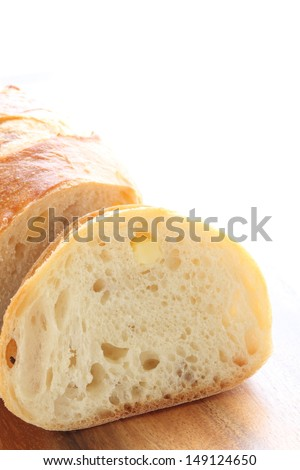 home made French bread,  baguette with cheese on wooden plate on white background - stock photo
