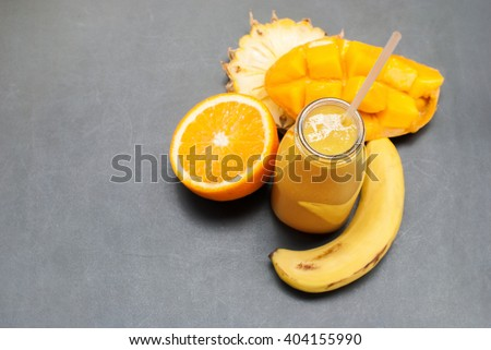Home Made Fresh Juices Smoothie Glass Bottles Yellow Fruits Orange Banana Mango Pine apple Vitamins Diet Healthy Concept Dark Background - stock photo