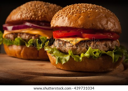 Home made hamburger with beef, onion, tomato, lettuce and cheese. Fresh burger closeup on wooden rustic table with potato fries and chips. - stock photo