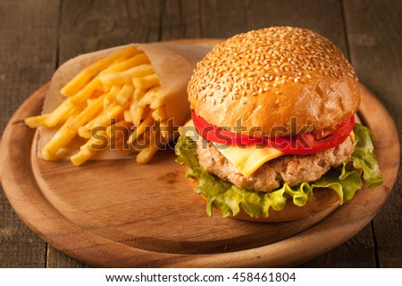Home made hamburger with beef, onion, tomato, lettuce and cheese. Fresh burger closeup on wooden rustic table with potato fries, beer and chips.