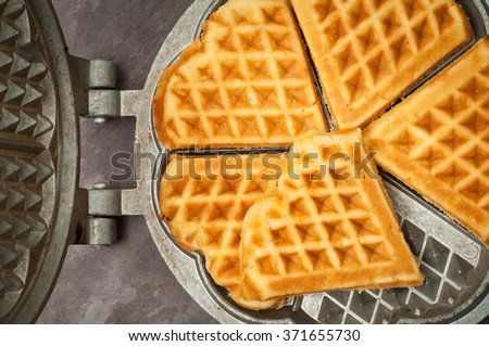 Home made heart shaped waffles served in a traditional cast iron waffle pan.