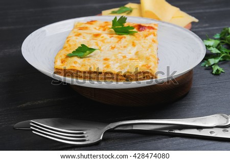 Home made meat lasagna with Bolognese sauce, pieces of cheese, green parsley on the plate on a dark black wooden background