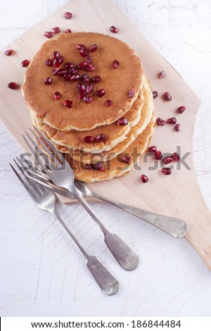 home made pancake with pomegranate seed on wooden board