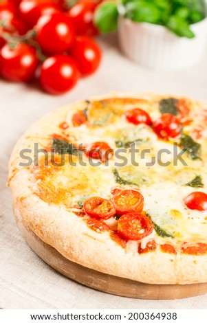 Home made pizza on wooden board with tomatoes on background. Selective focus, shallow DOF - stock photo