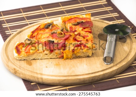 Home made pizza with salami, mushrooms, paprika and cheese on wooden board with pizza wheel knife and hot chili sauce on background