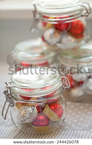 Home made pralines wrapped in silver and red foil - stock photo