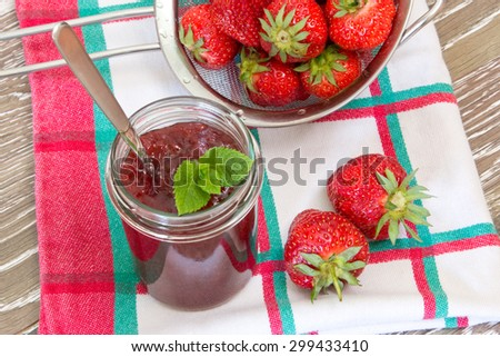 Home made strawberry jam with fresh fruits in a sieve - stock photo