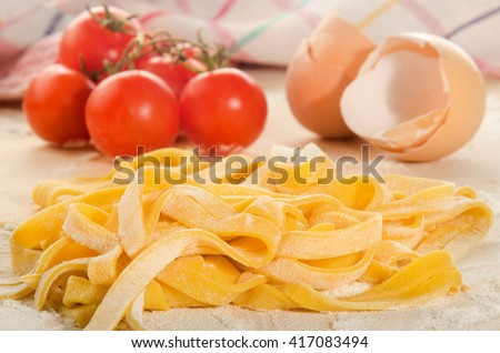 home made tagliatelle, tomato and egg on wooden board - stock photo