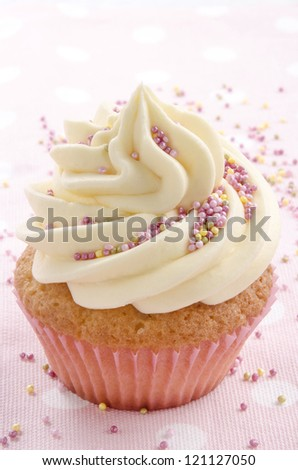 home made vanilla cupcake with colorful sprinkles - stock photo
