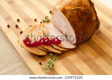 Home-made whole boiled chicken ham prepared by polish butcher. Presented on a wooden desk-board. Part of ham is cut to slices, shown with black pepper grains and cranberry marmalade. - stock photo