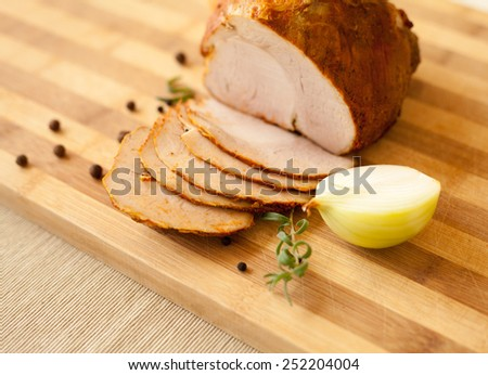 Home-made whole boiled chicken ham prepared by polish butcher. Presented on a wooden desk-board. Part of ham is cut to slices, shown with black pepper grains and onion. - stock photo