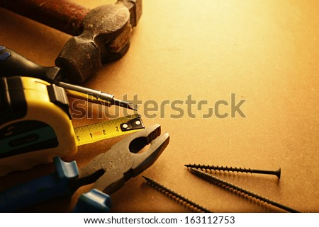 Home maintenance tool kit in a sepia toned image arranged in a semi circle on the border with a hammer, pliers, screwdriver, tape measure and nails surrounding copyspace
