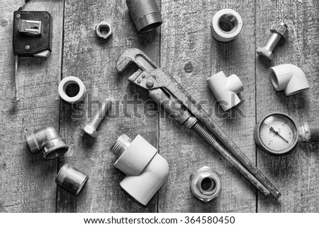 Home master concept. Tape-measure, internal screws, pipe screw, PVC pipe connectors, manometer on old wood table. top view.  - stock photo