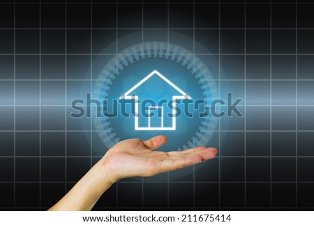 Home model in hand on dark background.