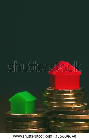 Home mortgage concept with small arrow-shaped plastic house models on top of stacked coins. - stock photo