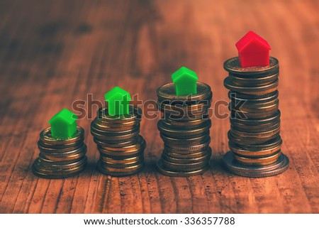 Home mortgage concept with small plastic house models on top of stacked coins. - stock photo