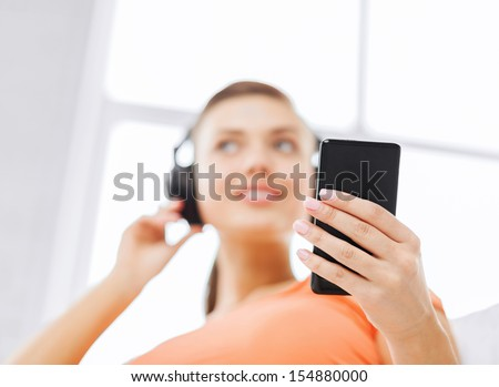 home, music, internet and shopping - woman with headphones and smartphone at home