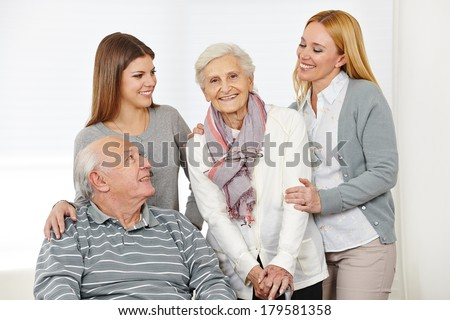 Home nursing for senior citizen couple with caregiver at home - stock photo