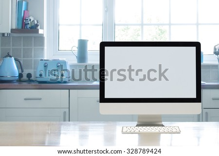 Home office interior set up in kitchen  with a blank computer screen to add copy - stock photo