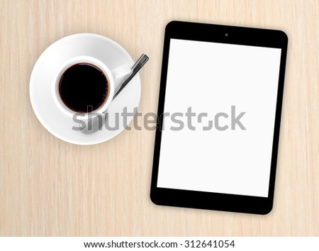 Home office. Tablet pc mockup on wooden table with coffee cup - stock photo
