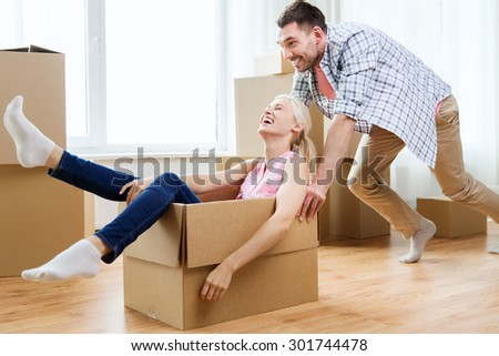 home, people, moving and real estate concept - happy couple having fun and riding in cardboard boxes at new home - stock photo