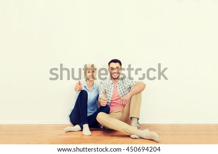 home, people, repair, moving and real estate concept - happy couple sitting on floor and showing thumbs up at new place - stock photo