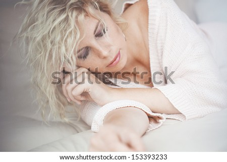 Home portrait of beautiful young woman resting in bed