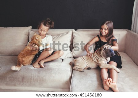Home portrait of two cute children hugging with ginger cat and puppy of Chinese Shar Pei dog on the sofa against black wall - stock photo